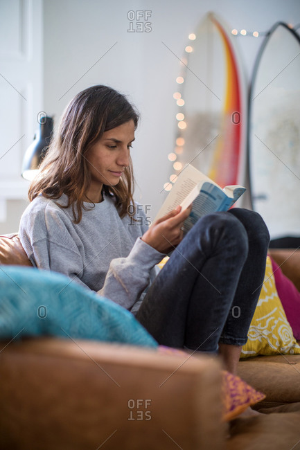 Young woman relaxing on living room sofa reading a book