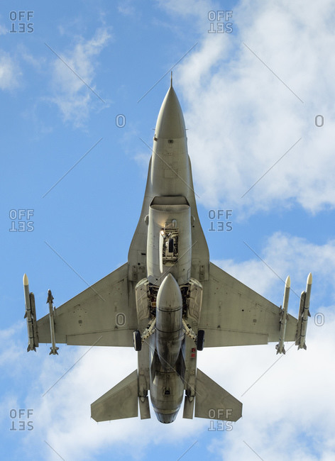 Polish F-16 fighter plane taking part in NATO exercise Frysian flag, low angle against blue sky, Netherlands