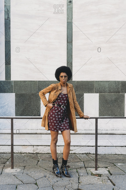 Young woman with afro hair resting against handrail in city