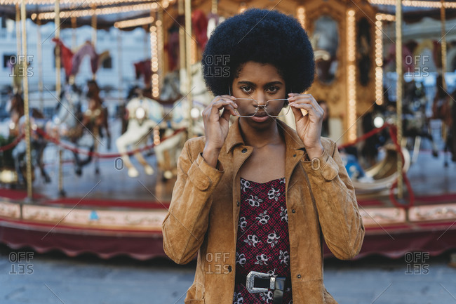 Young woman with afro hair putting on spectacles in front of carousel