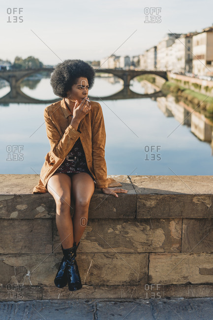 Young woman with afro hair smoking on bridge, Florence, Toscana, Italy