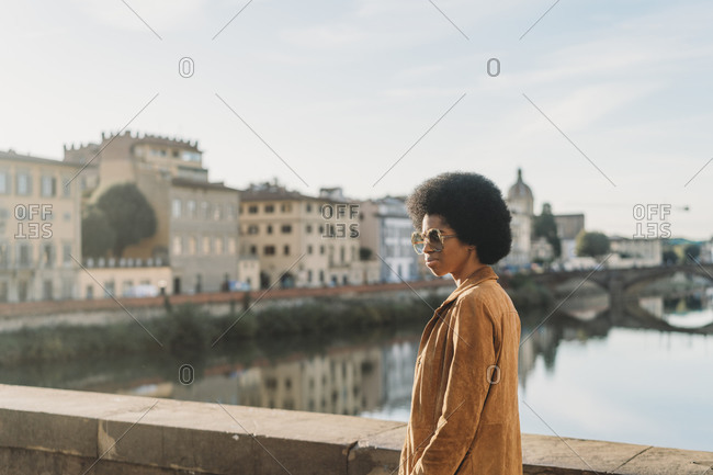Young woman with afro hair crossing bridge, Florence, Toscana, Italy