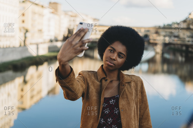 Young woman with afro hair taking selfie by canal, Florence, Toscana, Italy