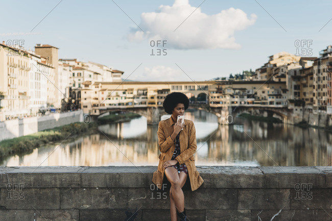 Young woman with afro hair waiting on bridge, Florence, Toscana, Italy