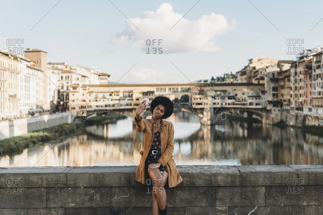 Young woman with afro hair taking selfie on bridge, Florence, Toscana, Italy