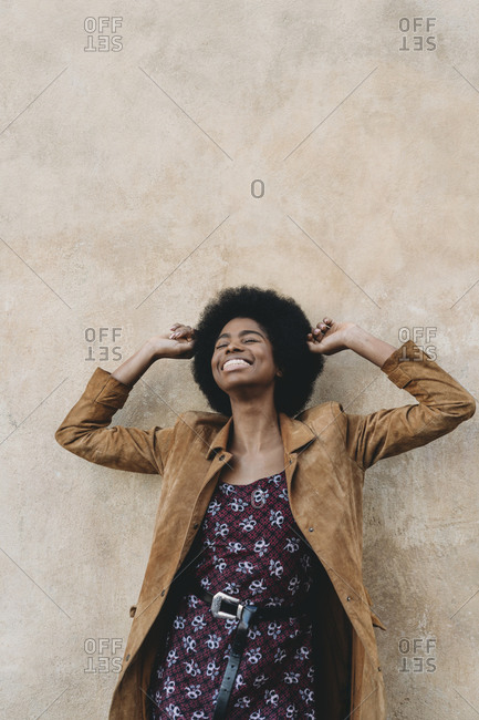 Young woman with afro hair feeling excited against stone wall