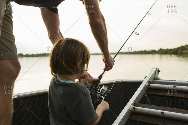 A five year old boy fishing from a boat on the Zambezi River, Botswana