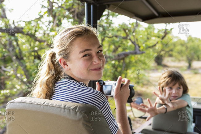 Two children, a teenage girl and young boy in a jeep in a game reserve