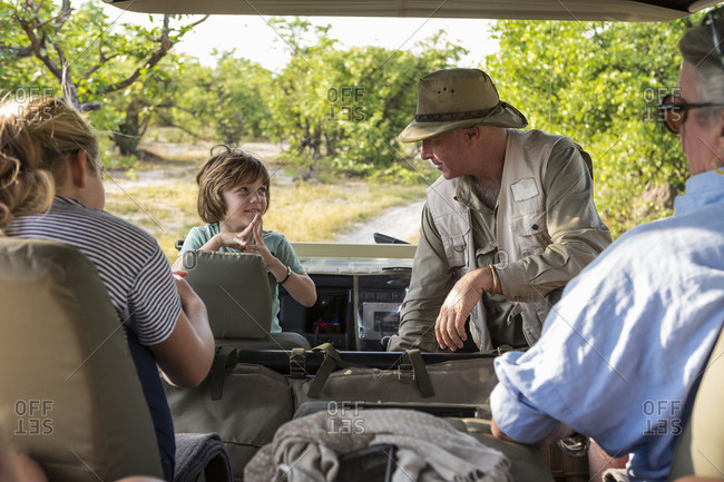 A family of visitors in a safari vehicle with a guide.