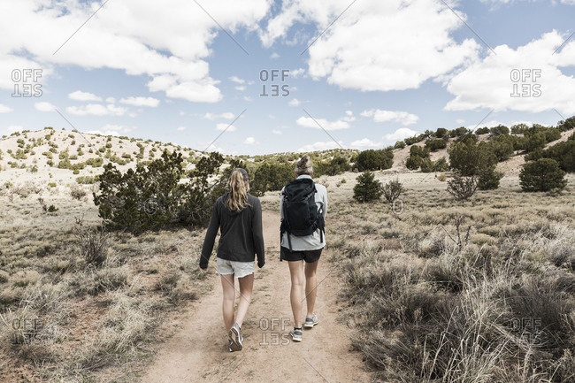 Rear view of adult woman and her teenage daughter hiking in the Galisteo Basin, NM.