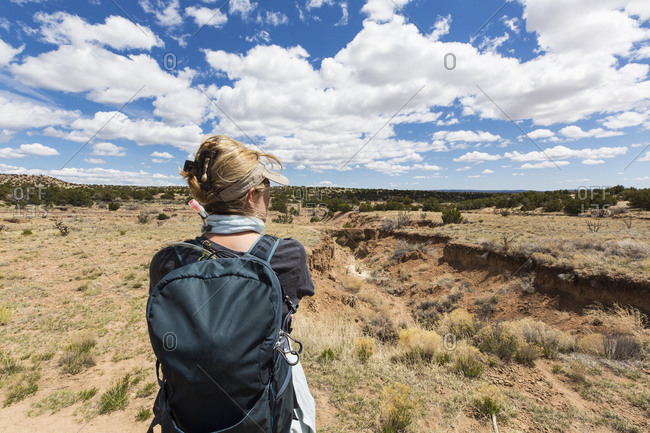 rear view of adult woman looking at Galisteo Basin, NM.