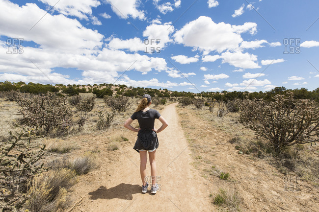 Rear view of 14 year old girl looking at dirt road, Galisteo Basin, NM.