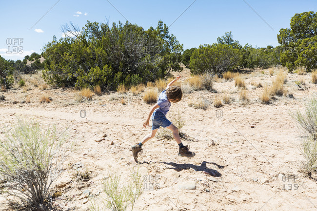 6 year old boy leaping on hiking trail