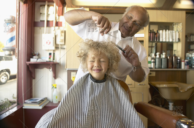 Young boy crying while barber cuts his hair