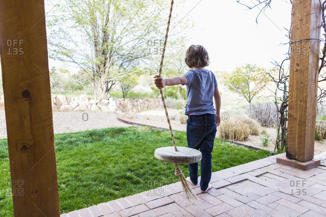Six year old boy using a rope swing on a wide porch in the shade.