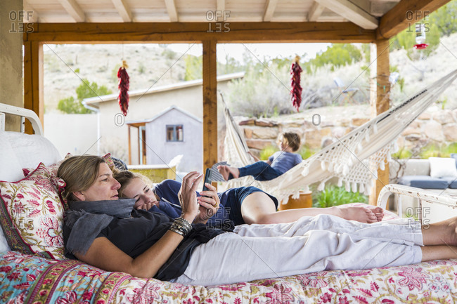 Mother and daughter lying together on an outdoor bed looking at a smart phone screen