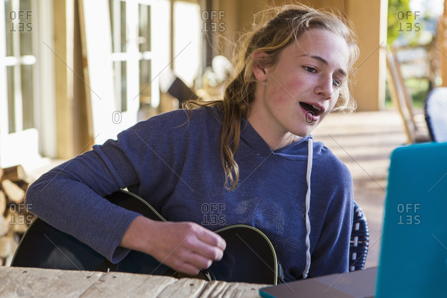 A teenage girl looking at laptop, singing and playing guitar