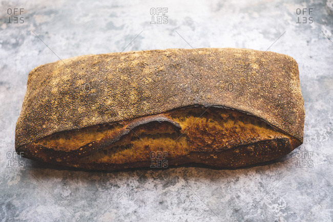 Artisan bakery making special sourdough bread, a baked loaf with firm dark crust.