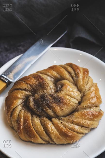 A platted glazed fresh baked cinnamon bun.