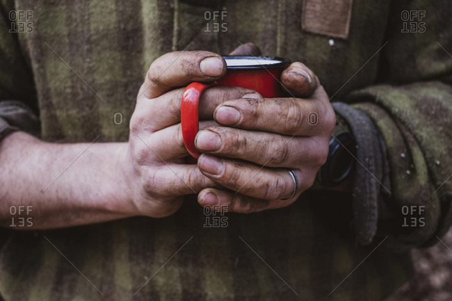 Close up of man with dirty hands holding red enamel mug.