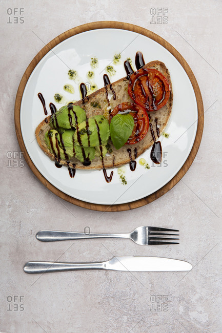 High angle close up of tomato and avocado bruschetta with balsamic vinegar reduction in a cafe.