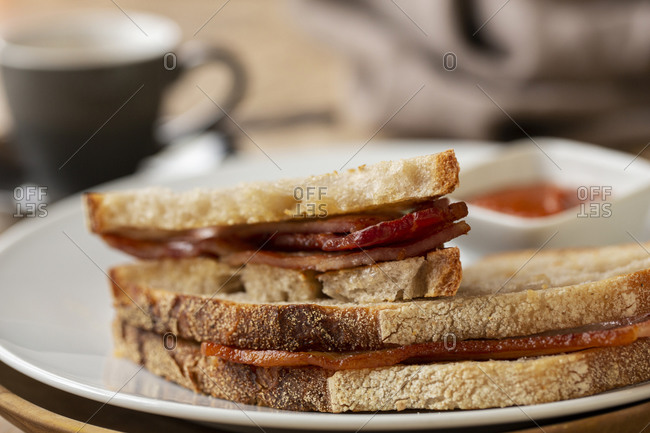 Close up of bacon sandwich and small bowl of home made tomato sauce in a cafe.