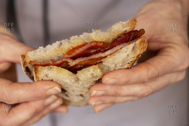 Close up of person holding bacon sandwich with tomato sauce.