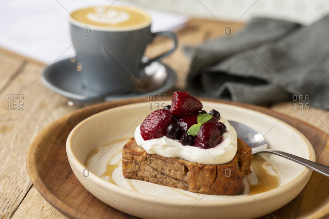 High angle close up of banana bread topped with yoghurt and mixed berries in a cafe.