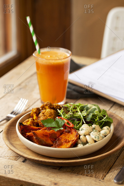 High angle close up of glass of carrot juice and bowl of mixed vegetables in a cafe.
