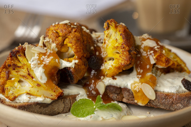 High angle close up of roasted cauliflower with yoghurt and sesame seeds on toasted sourdough bread in a cafe.
