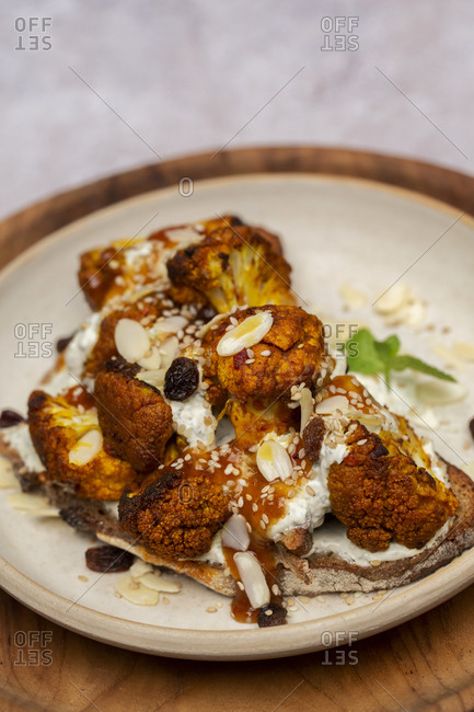 High angle close up of roasted cauliflower on toasted sourdough bread on a plate.