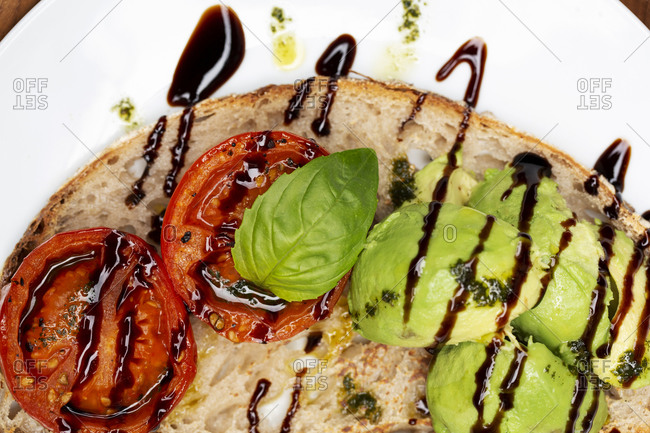 High angle close up of tomato and avocado bruschetta with balsamic vinegar reduction on a plate.