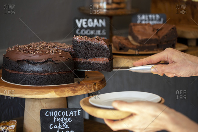 Close up of waitress putting slice of chocolate fudge cake on a plate door of a cafe.