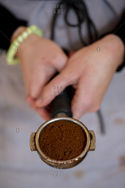 High angle close up of barista holding espresso machine portafilter.