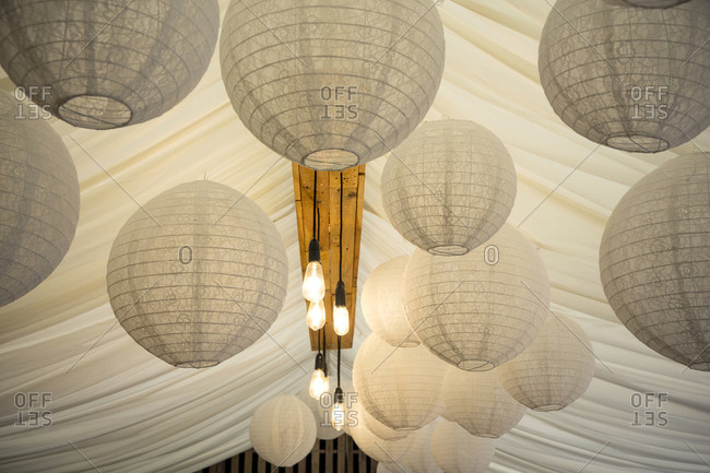 Detail of white Japanese Rice Paper lamps and fabric canopy, decorations for a naming ceremony in an historic barn.