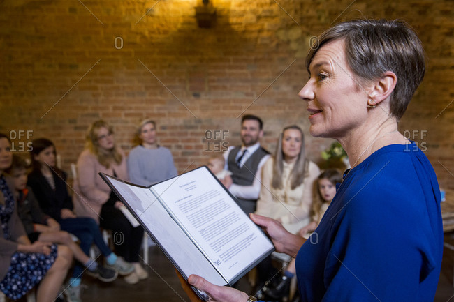 Celebrant performing naming ceremony for parents and their baby daughter in an historic barn.