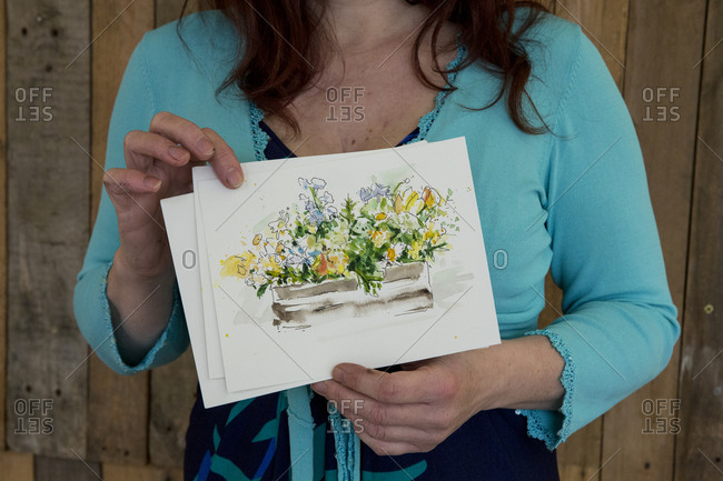 Close up of woman holding flower drawing during a naming ceremony.