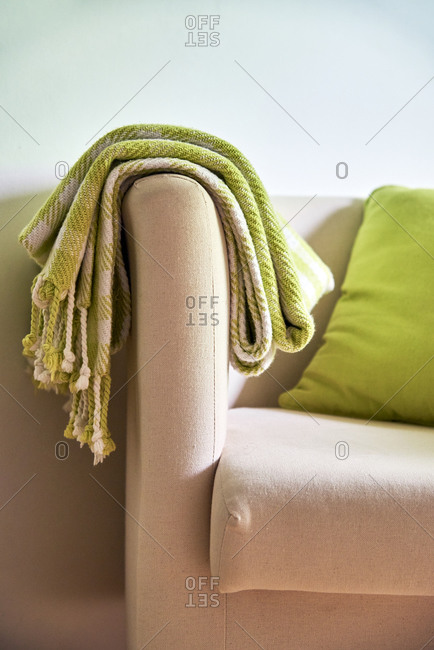 Green blanket draped over sofa arm