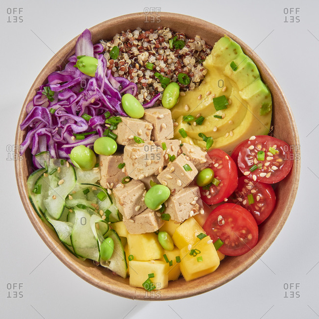 Poke bowl with tofu, avocado, mango, green beans, quinoa and cabbage isolated on white background