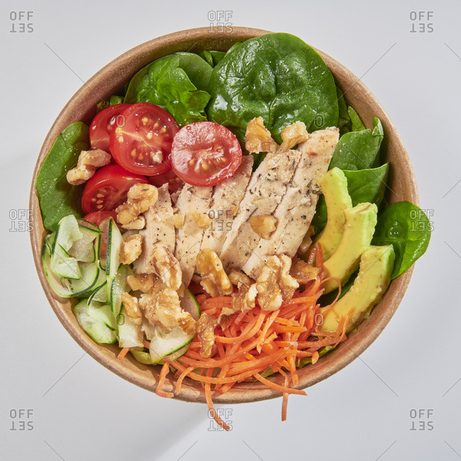 Poke bowl with chicken, avocado, carrots, spinach, cucumber and tomato isolated on white background