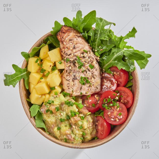 Poke bowl with salmon, guacamole, mango, arugula and tomato isolated on white background