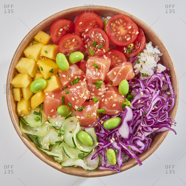 Poke bowl with smoked salmon, cucumber, mango, green beans, tomatoes, rice and cabbage isolated on white background