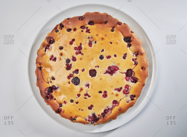 Homemade curd tart and red fruits isolated on white background