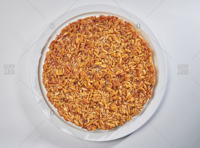 Almond tart with crunchy caramelized almond topping on white background