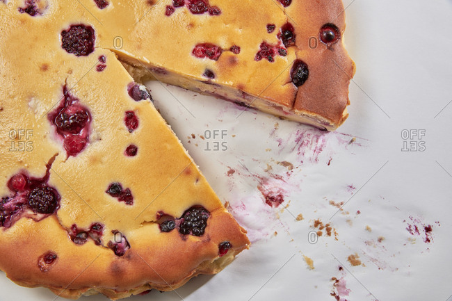 Homemade curd tart with red fruits missing a slice