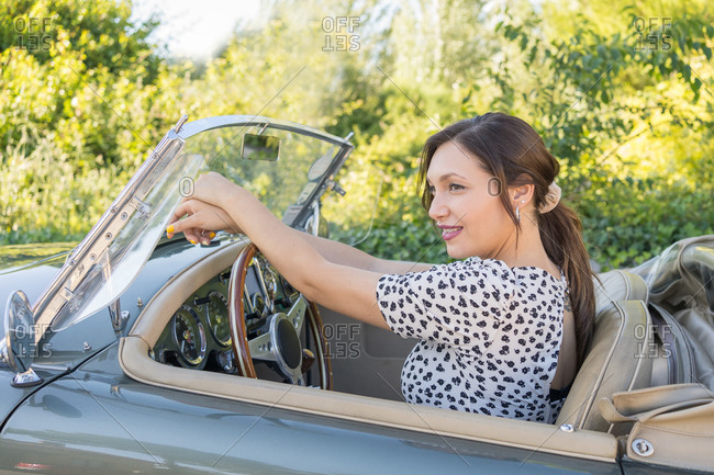 Beautiful and happy woman inside retro cabriolet car