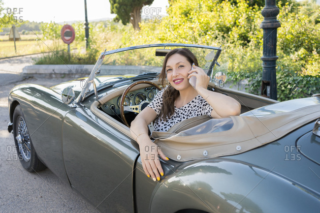 Elegant young woman in a convertible car off the road talking on the phone