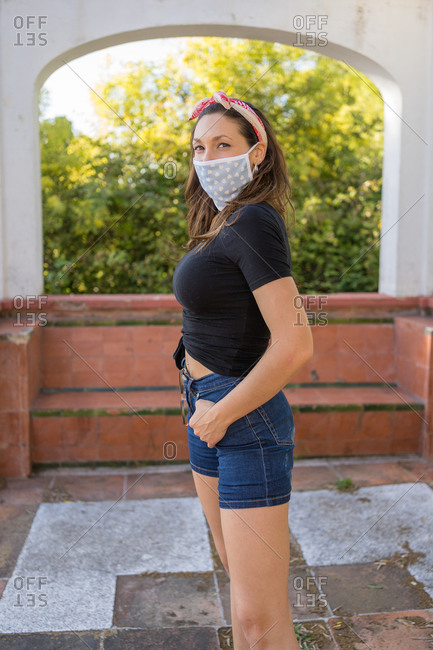 Pretty young woman in casual clothes and mask staring at the camera