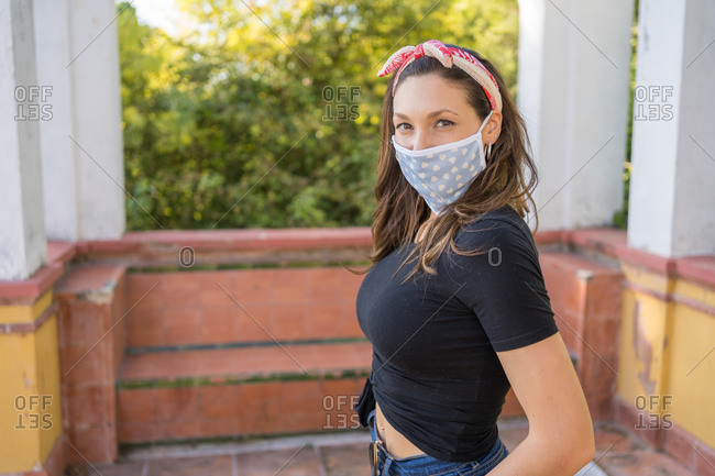 Attractive young woman in casual clothes and mask staring at the camera