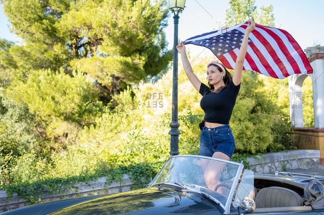 Young woman holding an American flag in a convertible car